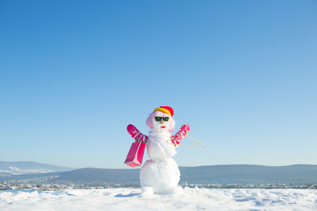 Foto de christmas female snowman in hat, mittens and glasses with shopping bag or gift pack with hanger at blue sky - Imagen libre de derechos