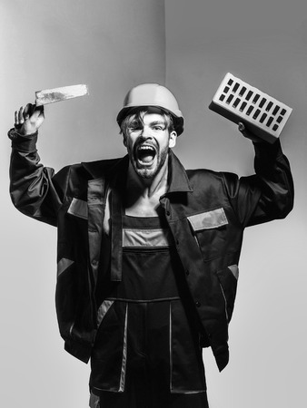 Foto de Excited man shouting handsome builder construction mason worker bricklayer in orange hard hat and boilersuit keeps brick and trowel on grey background - Imagen libre de derechos