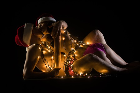 Photo for Relations of couple in illuminated garland. Santa man and girl with naked body. New year boyfriend and girlfriend isolated on black. Christmas couple in love of sexy man and woman. Love and sex games. - Royalty Free Image