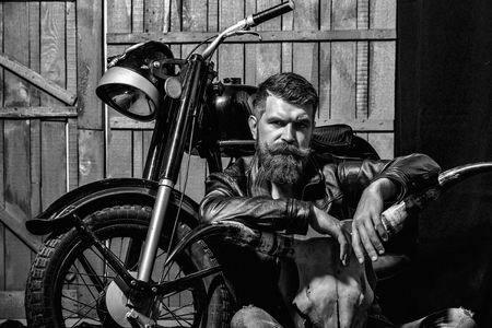 Photo pour Bearded man hipster biker brutal male with beard and moustache in leather jacket sits on floor near motorcycle with bone skull antlers on wooden background - image libre de droit