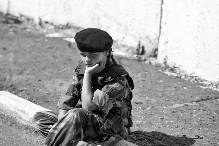 Foto de Young girl child with pretty sad thoughtful face in army camouflage ammunition and black beret sitting on stone ground outdoor - Imagen libre de derechos