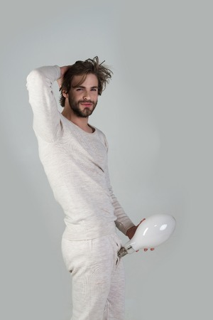 Foto de Solution and decision, big size. penis enlargement. Energy and electricity. Man with disheveled hair hold big lamp. Power? business success. Happy guy has an idea on grey background, morning, potency - Imagen libre de derechos