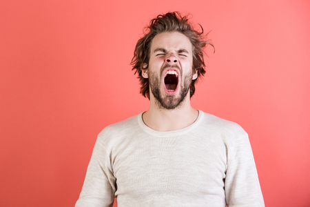 Photo pour Sleepy man with beard on red background. Insomnia, energy, single with uncombed hair. Morning wake up, everyday life. Barber and hairdresser, male fashion. Man with disheveled hair yawn in underwear. - image libre de droit