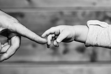 Photo pour Closeup of two touching hands of small baby boy holding finger of male father as symbol of family love and trust on blurred wooden background, horizontal picture - image libre de droit