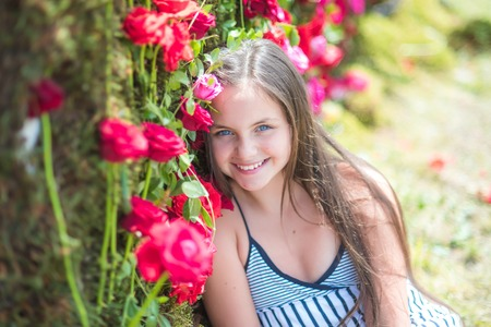Photo pour Little child with flowers, spring. Girl smile with red roses, beauty. Floristic, floral decor, design, flower shop. Beauty, spring, summer season. Valentines day, holiday celebration concept. - image libre de droit