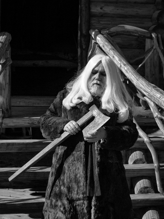 Foto de Old man druid with long silver hair and beard in fur coat stands with axe on log house background - Imagen libre de derechos