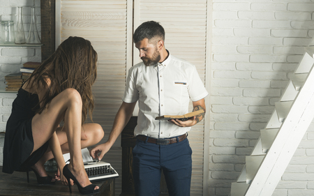 Foto de Hipster with sexy woman secretary type on vintage typewriter. Couple in office. Journalism, book, document, report. Retro style concept - Imagen libre de derechos