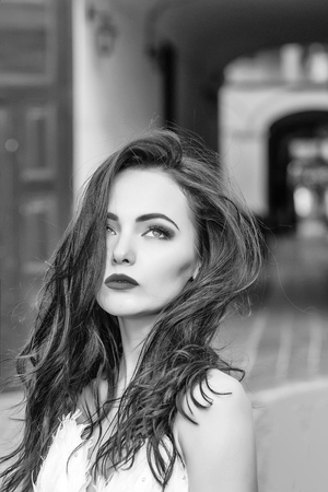 Photo for young sexy woman or girl with long black brunette hair and red lips on pretty face outdoor portrait on building background - Royalty Free Image