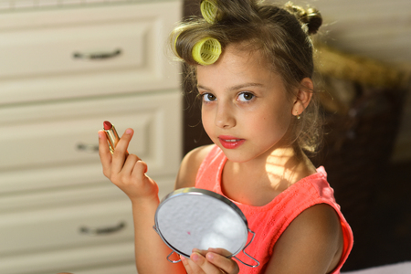 Photo pour Child sits on bed with pink lipstick and mirror. Little girl with curlers and cheerful face wears fashionable dress indoors. Kid with moms makeup accessories in room. Beauty and kids makeup concept. - image libre de droit