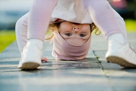 Photo pour Activity, energy concept. Girl stand on head on sunny day outdoor. Sport, yoga, pilates for child. Childhood, playtime, lifestyle. - image libre de droit