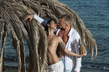 Photo for Topless woman and man kissing near umbrella made out of dried palm leaves. Couple with pineapple on vacation at tropical seashore. Love concept. Couple in love full of desire at beach, sea background. - Royalty Free Image