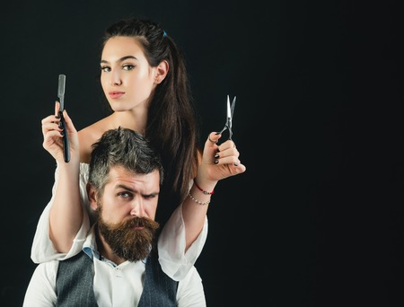 Photo pour Young handsome man with long beard and moustache on serious face with young woman cutting with scissors - image libre de droit