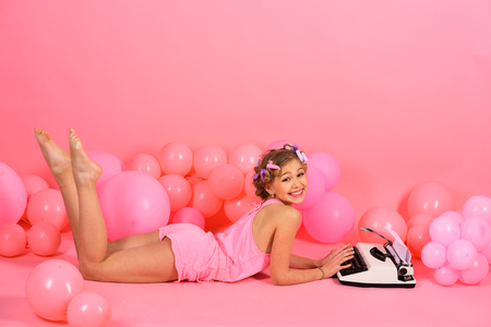 Photo pour Child in underwear with typewriter on pink background. Kid journalist or writer, career. Education and childhood. Little girl secretary at party balloons. Small girl with curler in hair typing. - image libre de droit