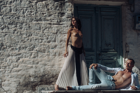 Photo pour Woman with naked breasts, man with nude torso lies outdoor. Sexy couple undressing under sunlight with ancient rocky wall and old door on background. Couple enjoys nudity. Passion and erotic concept. - image libre de droit