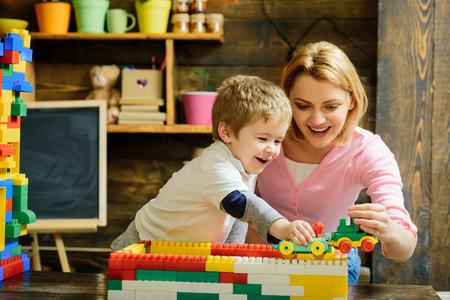 Photo pour Motherhood concept. Blond mom and son play with plastic building blocks train. Excited preschooler playing with his smiling mother or kindergarten teacher. - image libre de droit