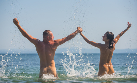 Foto de Sexy woman and man are free. Couple in love with sexy body relax on beach. Summer holidays and paradise travel vacation. Love relations of naked couple in sea water. happy family or valentines day - Imagen libre de derechos