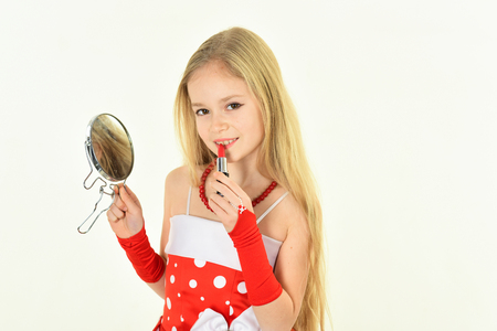 Photo for childhood and happiness. childhood, little girl pit red lipstick on lips with mirror - Royalty Free Image
