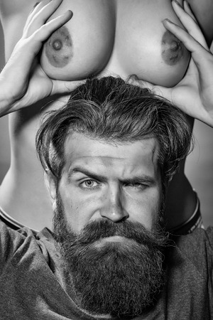 Photo pour man with serious emotion. Bearded man and bare female chest - image libre de droit