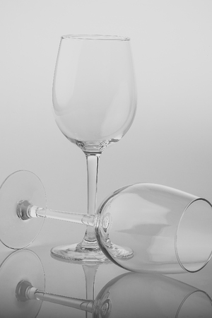 Photo pour Closeup of two transparent clear crystal empty wine glasses standing and lying isolated on chrome white and grey background, vertical picture - image libre de droit