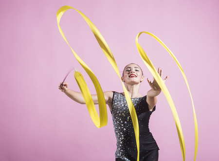 Photo pour ribbon for rhythmic gymnastics at sport woman. ribbon for rhythmic gymnastics in hand of girl on pink background. - image libre de droit