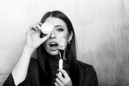 Photo pour womens cosmetics. sexy pretty brunette woman face with artist or makeup brush - image libre de droit