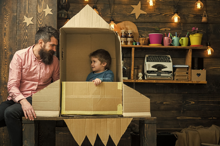 Photo pour dreams of space. Kid happy sit in cardboard hand made rocket. Boy play with dad, father, little cosmonaut sit in rocket made out of cardboard box. Rocket launch concept. Child cute boy play cosmonaut, astronaut. - image libre de droit