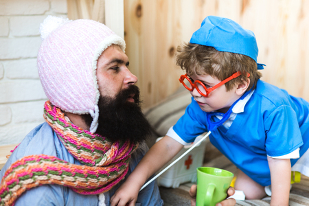 Foto de Consulting on the go. Son in glasses with stethoscope examine father at home. Little child play doctor with man. Medicine and health. Boy in doctor uniform treat patient. Game and development - Imagen libre de derechos