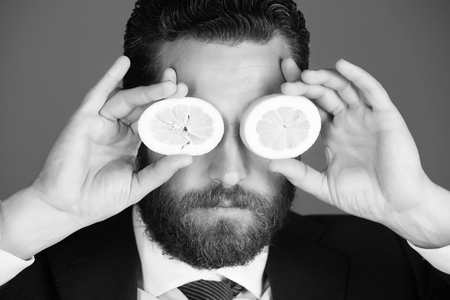 Foto per healthy food and dieting. lemon at face of man with beard or businessman - Immagine Royalty Free