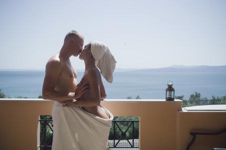 Foto de couple in love wrapped in a towel, hugging and kissing on the balcony - Imagen libre de derechos
