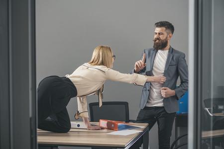 Photo pour Businesswoman seducing boss man at office table - image libre de droit