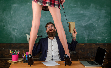 Foto de Sex education. Anatomy lesson and sex education in high school. Lets Talk Sex. Bearded sexology teacher looks at two sexy female students. Erotic education and sex Symbols on chalkboard. - Imagen libre de derechos