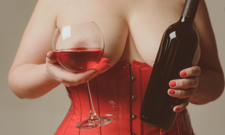 Photo pour Sexy Plus Size Lingerie. Be Sexy. Woman in red holding wine glass. XXL big size. Female breast. Beautiful girl shows her gorgeous Breasts. - image libre de droit