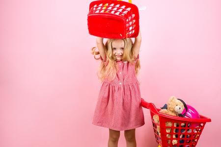 Foto de I always say shopping is cheaper than a psychiatrist. Happy little girl shopping. Little shopaholic with shopping cart. - Imagen libre de derechos
