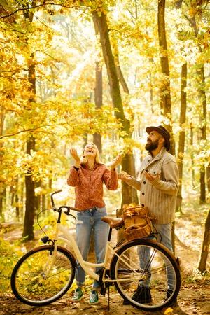 Foto de Autumn couple is riding the bicycle in the park. Active people. Outdoors. Autumn woman an bearded man with retro bike in autumnal park. Couple with vintage bike. - Imagen libre de derechos