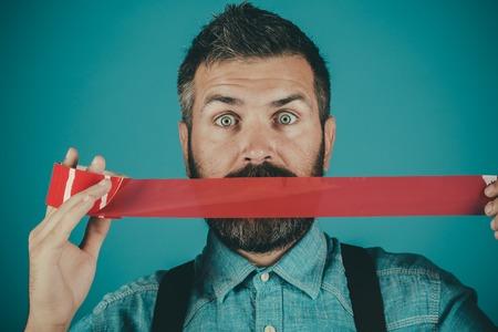 Foto de man wrapping mouth by adhesive tape. - Imagen libre de derechos