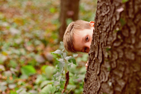 Photo for The thrill is in the discovery. Small boy play hide and seek. Small boy enjoy playing outdoor. Its a game of hide-and-seek. Its fantastic game - Royalty Free Image