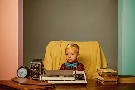 Foto de Little boy type research paper on typewriter. Child typewrite research work at desk. - Imagen libre de derechos