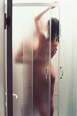 Photo pour Undressed couple kissing passionately in the shower. - image libre de droit