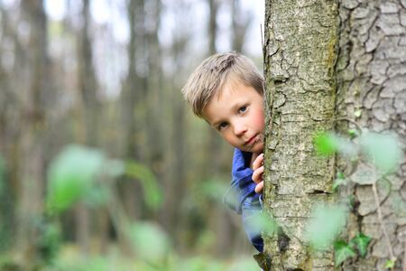 Photo for Enjoying my childhood. Little boy have fun in woods. Little boy play hide and seek. Outdoor games is my childhood - Royalty Free Image