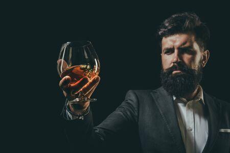 Photo pour Bearded businessman in elegant suit with glass of cognac. Luxury beverage concept. Man Bartender holding glass of cognac. - image libre de droit