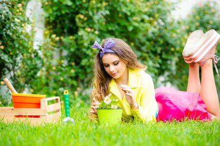 Potted plant, potting concept. Teenager girl holding flowers pot. Spring day.