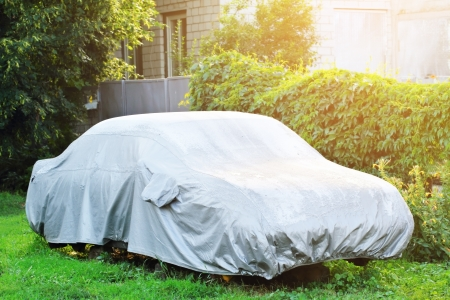 Photo pour A parked car with protective cover in wet weather  - image libre de droit