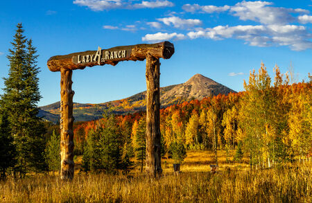 Colorado Lazy Ass Ranch entrance at sunset on warm fall evening with Hahn Peak in distance and changing yellow Aspen trees on mountain slopes