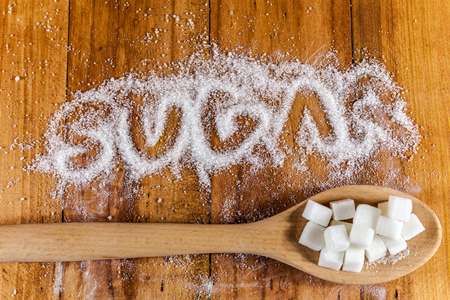 Photo for The word sugar written into a pile of white granulated sugar with spoon of sugar cubes over wooden background - Royalty Free Image