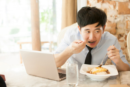 Photo pour Young Asian man working while eating with his laptop in restaurant (selective focus) - image libre de droit