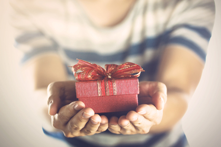 Photo for Young man giving and presenting a gift to someone. - Royalty Free Image