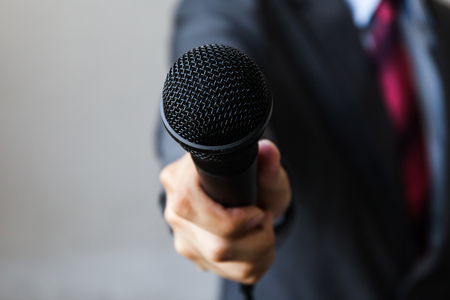 Photo pour Man in business suit holding a microphone conducting a business interview, journalist reporting, public speaking, press conference, MC - image libre de droit