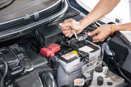 Foto per Mechanic engineer fixing car battery in garage (selective focus). - Immagine Royalty Free