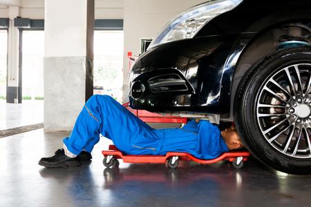 Photo pour Mechanic in blue uniform lying down and working under car at auto service garage - image libre de droit