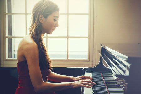 Photo for Asian woman playing piano in window background with light coming in (Vintage tone) - Royalty Free Image